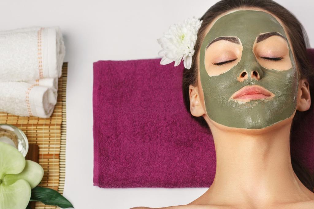 Mulher com rosto coberto por máscara de argila verde,sobre uma toalha de cor lilás. No canto esquerdo há uma esteira de vime com toalhas e flores brancas.